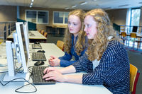 Two dutch students working on computer in school