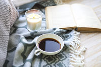 Cup of coffee, candle and book on the floor