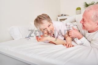 Senioren albern auf dem Bett herum