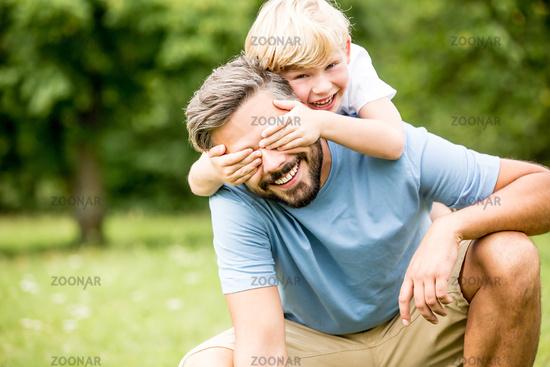 Sohn hält seinem Vater die Augen zu
