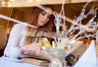 Young brunette reading a book and drinking a coffee in a restaurant