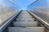 Metal escalator outdoors with blue sky