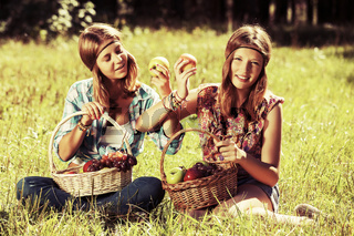Happy young fashion girls with a fruit basket on nature