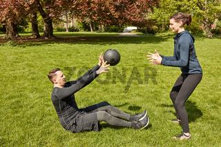 Mann wirft Gewichtsball zu Personal Trainer