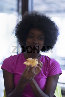 woman with afro hairstyle eating tasty pizza slice