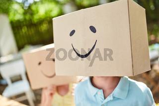 Kind unter einem Pappkarton mit Gesicht