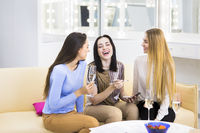 Girls talking, trying cosmetics and drinking champagne
