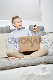 Seniorin liest eines SMS auf der Couch