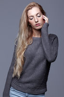 Portrait of young woman in gray woolen sweater. Beautiful girl posing on grey studio background. Female with blonde hair and day beauty makeup