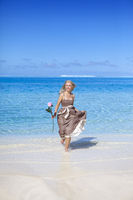 The beautiful woman with a rose on the edge of the sea on a beach