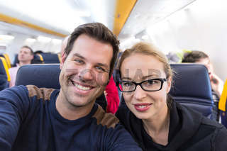 Young handsome couple taking a selfie on commercial airplane.