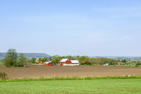 Landscape view with fields and farms in the swedish countryside in spring
