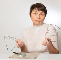 Woman holding two glasses in her hands. Bad vision