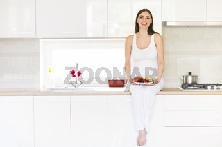 Pregnant woman with fruits on the plate
