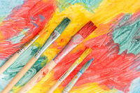 Five watercolor brushes on abstract painting