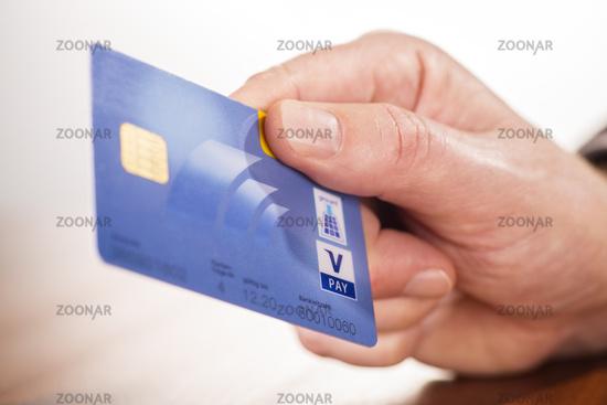 Hand mit Girocard der Postbank