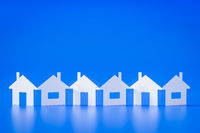a paper cutout row of houses blue background