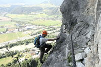 Mann klettert die Felswand rauf