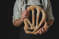 Baker's hands hold fougas bread