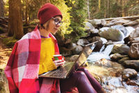 Hipster girl designer with a plaid on her shoulders in a hat and a yellow sweater and glasses with a laptop on her lap and a mug of coffee in her hands, look at the laptop screen sitting on a stone in a pine forest next to a mountain river. The concept of