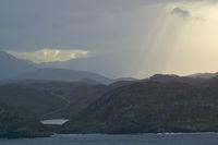 Berge und See mit wolkigem Himmel und Sonnenstrahl