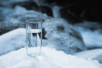 A transparent glass glass with drinking mountain water stands in the snow against a background of a clean frost mountain river in winter.