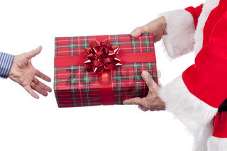 Father christmas handing over a tarten wrapped present with a red bow on a pure white background