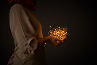 Girl holding yellow garland lights