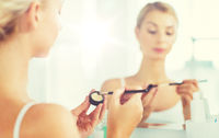 woman with makeup brush and eyeshade at bathroom