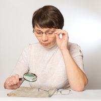 Vision problems. Woman with glasses and a magnifying glass reading a newspaper