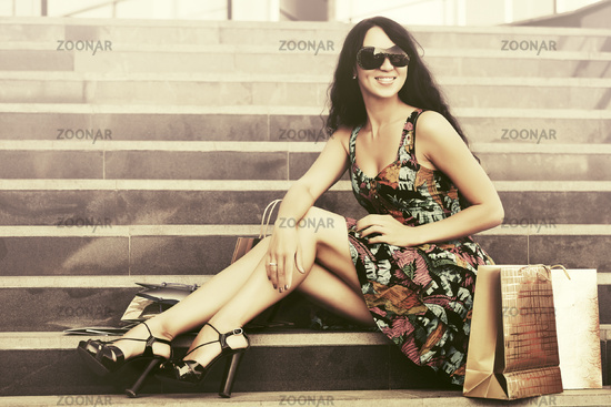 Happy young fashion woman with shopping bags sitting on mall steps