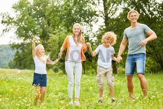 Familie und Kinder tanzen fröhlich im Garten