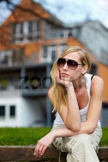 Frau wartet vor Haus