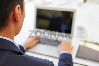 Geschäftsmann programmiert am Laptop