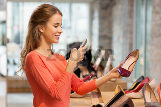 woman taking photo by smartphone at shoe store