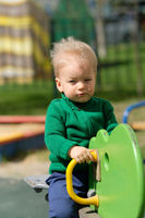One year old baby boy toddler wearing green sweater at playground