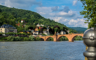 Carl Theodor bridge and Nekkar river embankment with many houses and a hill at the background on sunny summer evening, Heidelberg, Germany.
