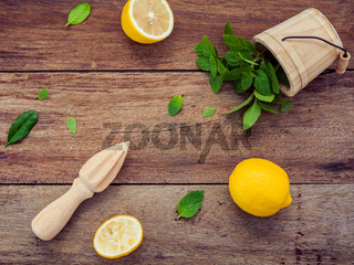 Fresh lemon and wooden juicer for summer juice and cocktail. Fresh lemon sliced and peppermint leaves set up on shabby wooden background flat lay.