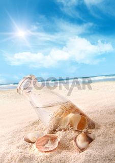 Bottle with seashells in the sand