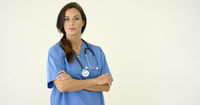 Woman in scrubs crosses arms and smiles at camera