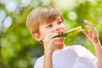 Hungriger Junge isst eine gesunde Wassermelone