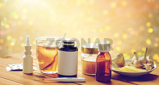 drugs, thermometer, honey and cup of tea on wood