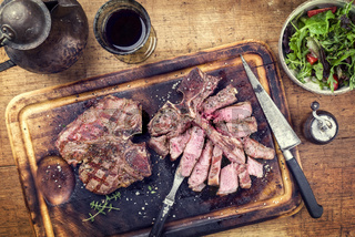 Two Barbecue dry aged Wagyu Porterhouse Steaks with Rocket Salad as close-up on a cutting board