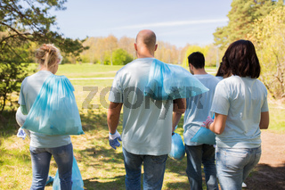 group of volunteers with garbage bags in park