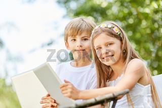 Junge und Mädchen lernen Umgang mit dem Tablet