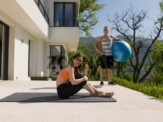 woman and personal trainer doing exercise with pilates ball