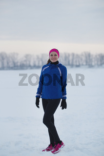 Portrait of a smiling young female sportswoman in winter ice field