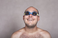 Funny man in swimming goggles daydreaming and looking up