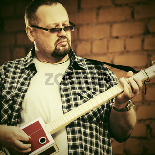 Handsome man playing his cigar box guitar
