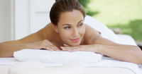 Curious woman on spa table wrapped in white towels